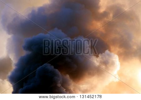 thick dark smoke in a fire against the sun