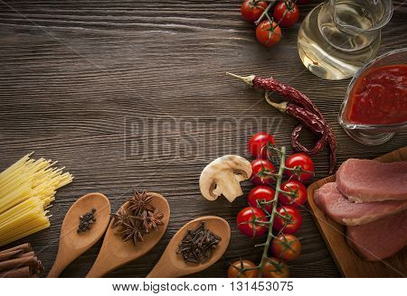 everything on wood table for the cooking of acute Italian sauce (tomato garlic spices olive oil)