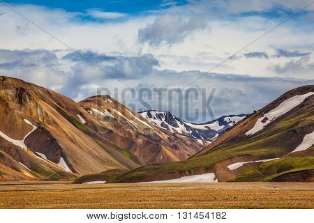 Magnificent Iceland in the summer. Valley National Park Landmannalaugar. On the gentle slopes of the mountains are snow fields and glaciers