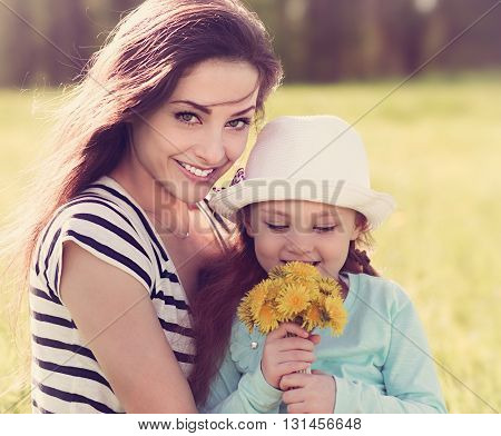 Beautiful Young Mother Embracing Her Cute Daughter With Yellow Bright Flowers On Summer Background.