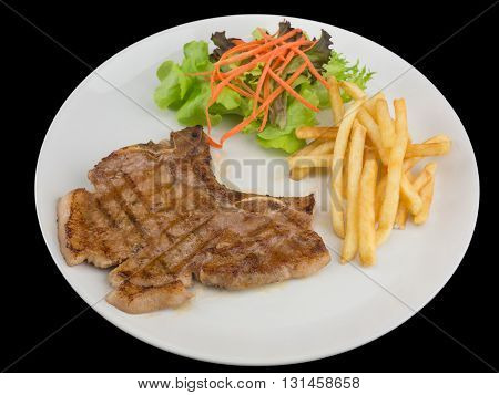 Tender grilled porterhouse or t-bone steak served with golden French fries and fresh green herb salad isolated on the black background with clipping path