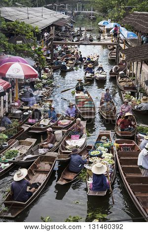 RATCHABURI THAILAND -Oct 3: Wooden boats are loaded with fruits from the orchards at Tha kha floating market on October 3 2015 in RatchaburiThailand. A traditional way still practiced in Tha kha canals of Thailand.