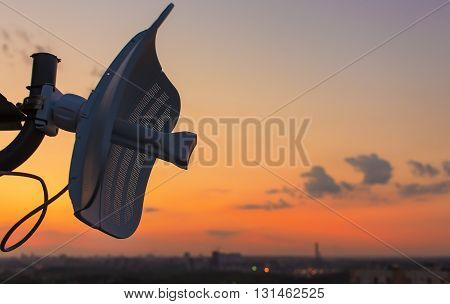 broadcasting antenna in the form of plate against the background of a beautiful sunset over the city