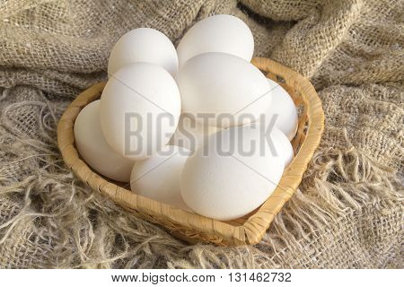 white eggs in a straw plate against the background of the canvas