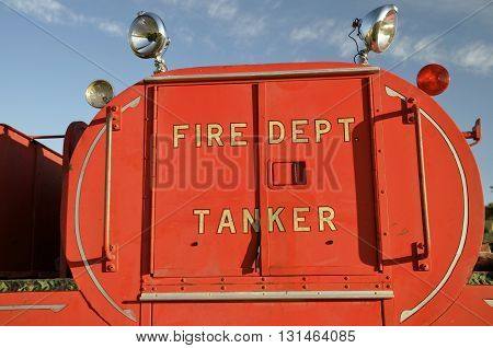 A vintage fire truck tanker with flood lights is in excellent condition.