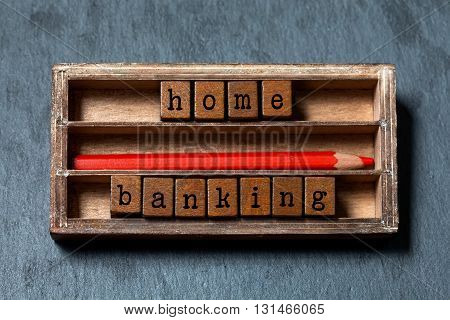 Home banking, budgeting concept image. Wooden boxes with letters, red pencil, aged box. Gray stone background, soft focus