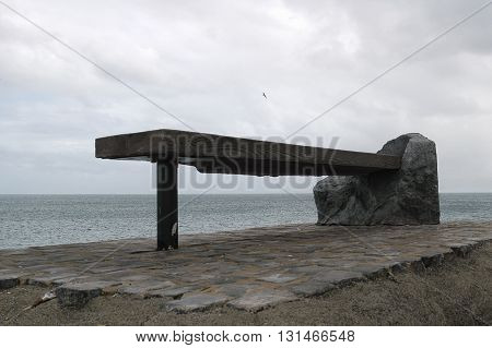A shot of a bench next to the see under a seagull on the fly