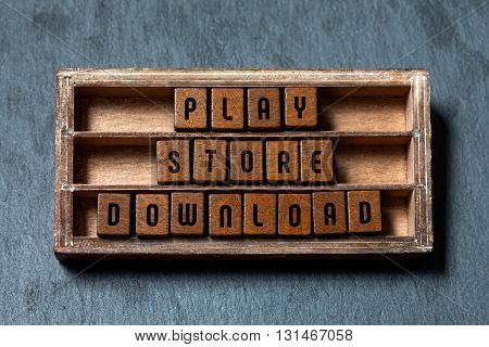 Play store download. Conceptual phrase image. Wooden blocks with letters, aged wood frame. Gray stone background, close-up
