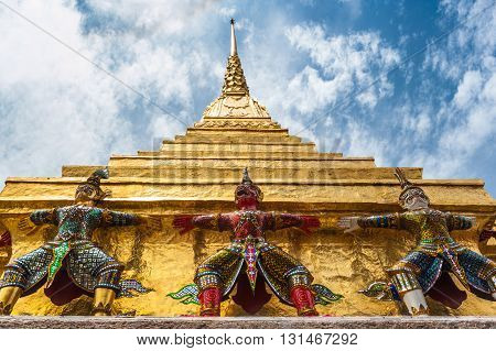 Yakshas and golden stupa Wat Phra Kaew, Bangkok, Thailand. Low angle view