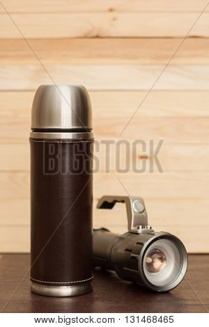 Thermos Bottle With A Flashlight On The Table.
