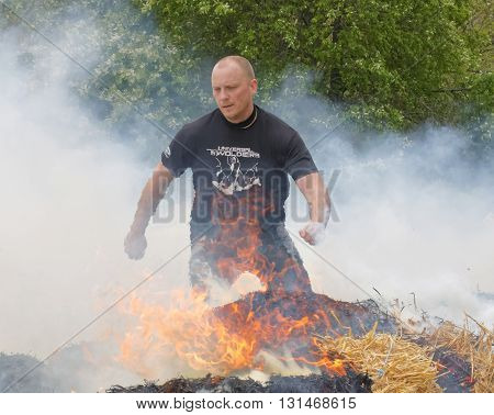STOCKHOLM SWEDEN - MAY 14 2016: Man in black clothes jumping over fire and smoke in the obstacle race Tough Viking Event in Sweden April 14 2016
