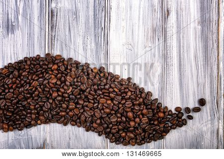 Coffee Beans Stacked  On The Old Wooden Background