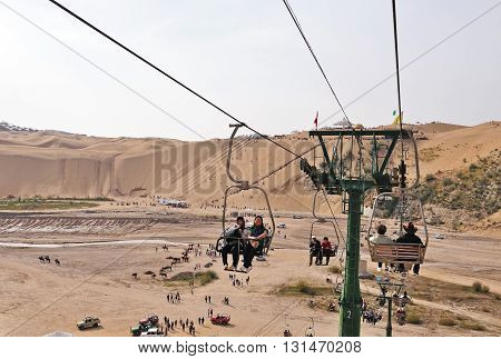 ORDOS CHINA - OCTOBER 3, 2012: Tourists riding the cable car in Kubuqi desert park the cable car takes riders to the top of the desert. Kubuqi desert is a tourist's attraction in Inner Mongolia.