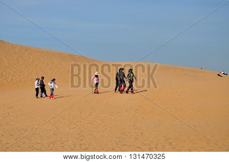 ORDOS CHINA - OCTOBER 3 2012: Tourists at Kubuqi desert park near Ordos city. The desert is the seventh biggest desert in China and one of tourist's attraction in Inner Mongolia.