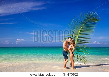 Couple in love with palm leaves on a wild beach. Thailand. Bikini. Lost heaven. Paradise.