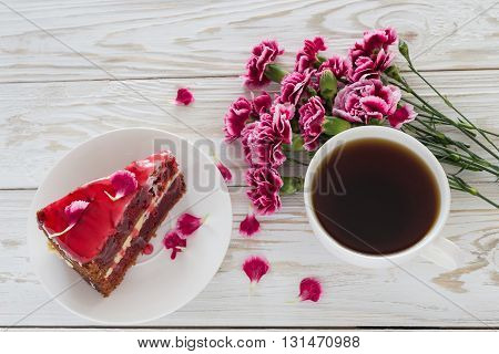 Red velvet cake, cup of coffee and pink carnations on wooden table