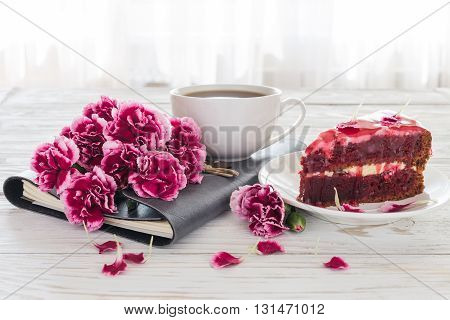 Red velvet cake, cup of coffee, notebook and pink carnations on wooden table