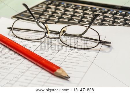 Real workflow house accountant. Documents pencil glasses keyboard.