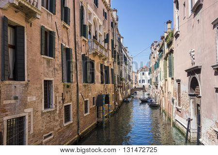 Boats on small canal among old old houses in Venice, Italy.