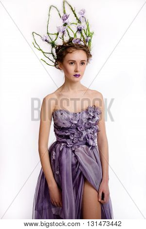 Fashion shot of beautiful young woman in elegant designer purple dress with crown on white blackground