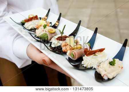Detail of waiter holding canapes on plastic spoons.