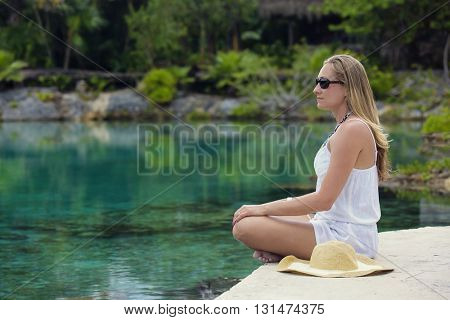 Beautiful woman relaxing and meditating in a jungle pool at a tropical island resort