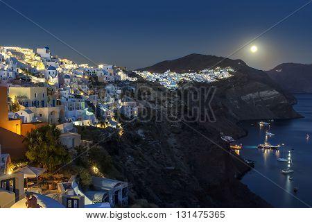 Moonrise in Oia village at night in Santorini island, Greece.