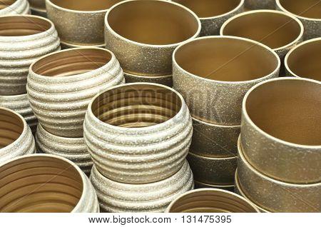 Group of gold flower ceramic pots on the shelves