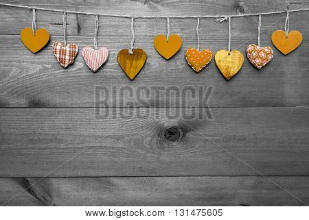 Wooden Background With Orange Hearts Hanging In A Row. Black And White Style With Colored Hot Spots. Copy Space For Advertisement Or Free Text. Greeting Card For Mothers Or Valentines Day