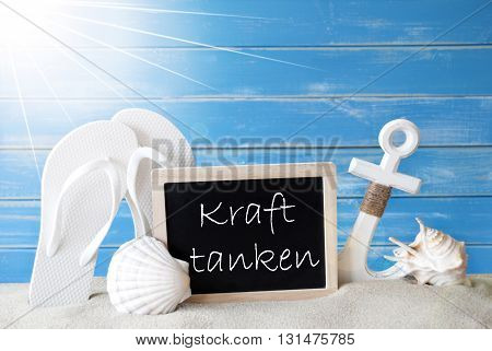 Chalkboard With German Text Kraft Tanken Means Relaxation. Blue Wooden Background. Sunny Summer Card With Holiday Greetings. Beach Vacation Symbolized By Sand, Flip Flops, Anchor And Shell.