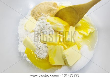 ingredients for shortcrust pastry as flour eggs butter and sugar with a stirring spoon in a bowl baking background view from above selected focus narrow depth of field