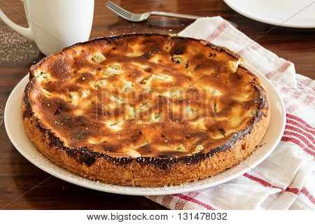 pie or cake with rhubarb and cottage cheese fresh from the oven with a kitchen towel on a brown table selected focus narrow depth of field