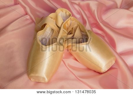 Ballet shoes on delicate pink silk background