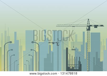 view of the city with tower cranes and street lamps in the foreground
