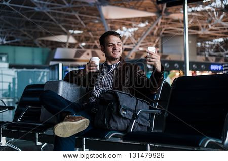 Portrait of a young man laughing and taking selfie with coffee at the airport waiting his flight.