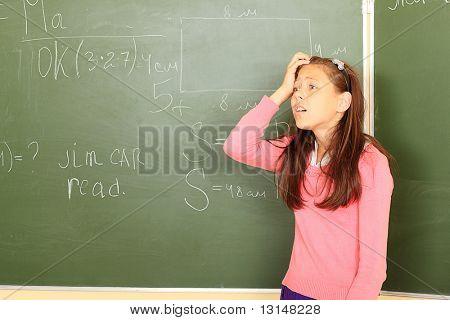 Educational theme: funny schoolgirl in a classroom.