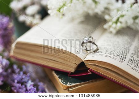 Pair of wedding rings with diamond. Rustic background with old books and lilac flowers. Retro background. Selected soft focus.