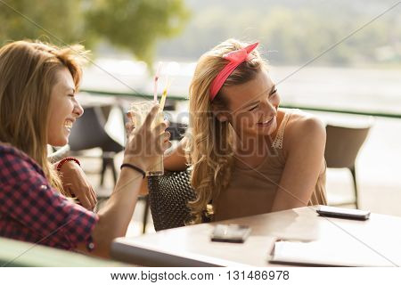Beautiful young girls sitting in an outdoor cafe drinking coffee and having fun photographing each other