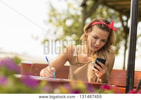 Beautiful attractive blond girl sitting in an outdoor cafe holding a mobile phone and writing notes