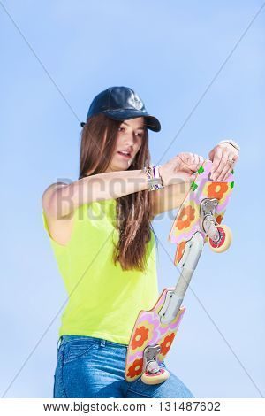 Summer sport and active lifestyle. Cool teenage girl in skater with skateboard on the street. Outdoor.