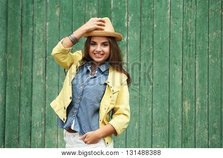 Pretty young woman in hat on green wood background