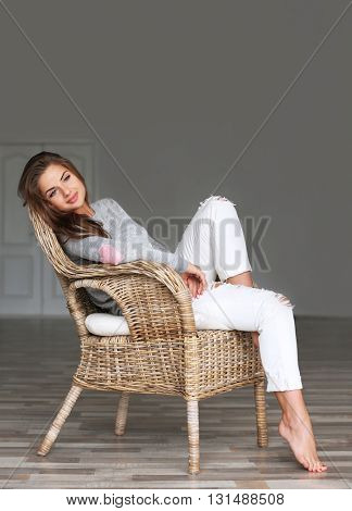 Pretty young woman sitting in armchair on gray background