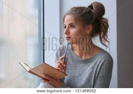Beautiful young woman sitting with notebook on windowsill