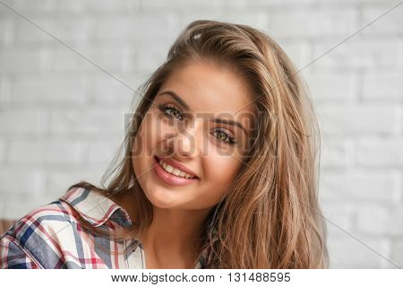 Young long-haired woman on brick wall background