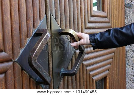 Lady's hand opening heavy bronze door. Hand and door handle. Hand touching door handle.