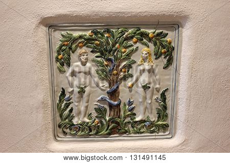 Adam and Eve ceramic tile.  Adam and Eve in Eden garden. Folk art ceramic tile. Adam and Eve scenery.