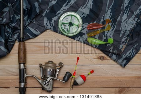 Set for fishing on the wooden background with camouflage clothing. Reel fishing line floats spinning fishing rod. Fishing and recreation.