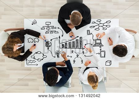 High Angle View Of Professional Businesspeople Making Various Business Chart