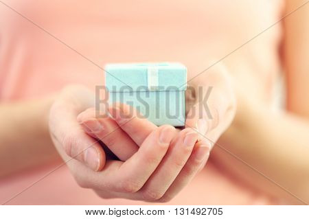 Female hands holding beautiful small gift wrapped with satin ribbon.