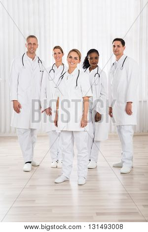 Group Of Happy Doctors With Stethoscope Standing In Hospital